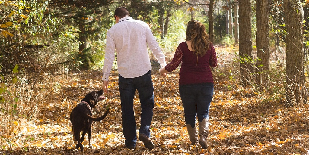 Man and lady walking in woodland with a dog