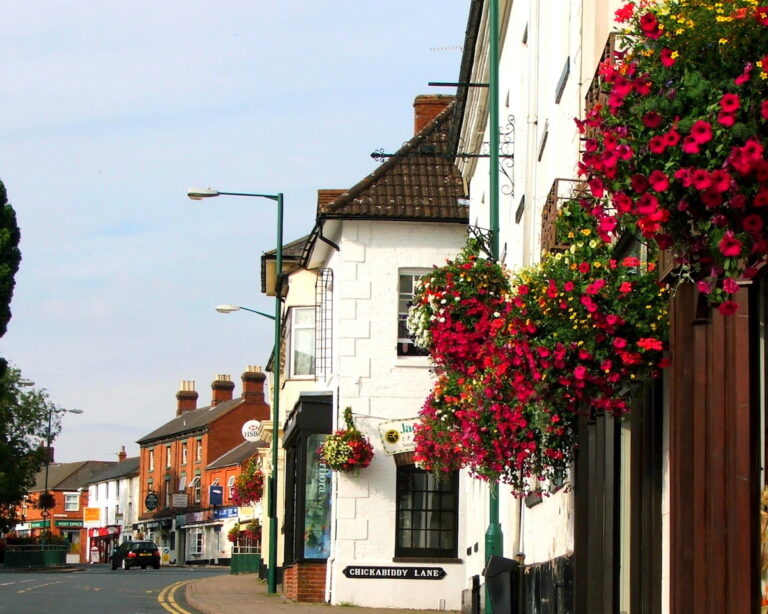 View of Southam High street with hanging baskets outside a shop